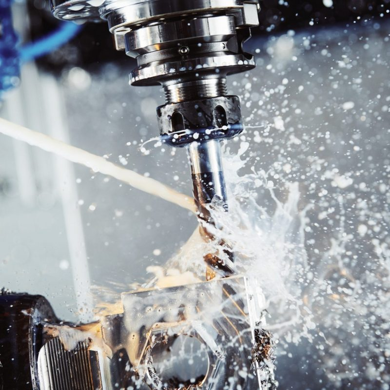 Milling metalworking process. Industrial CNC metal machining by vertical mill. Coolant and lubrication
